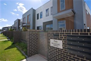 Polo townhouses mid shot west view with name plate
